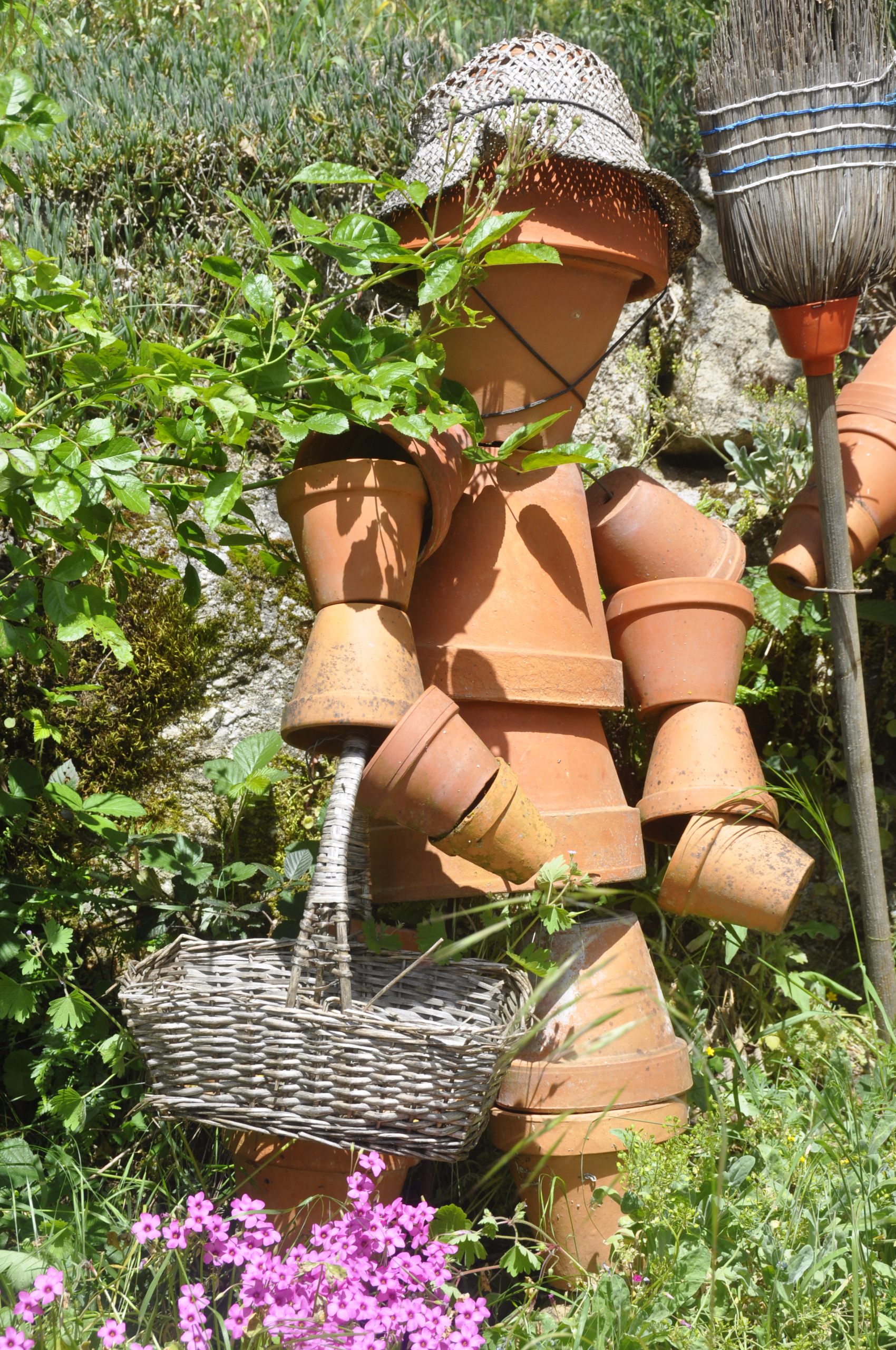 Stacked terra cotta flower sculpture that looks like a gardener