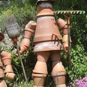 Stacked terra cotta flower sculpture that looks like a gardener holding a rake and broom