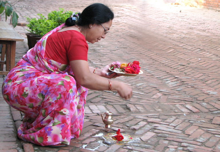 Woman in pink and red flowered garment performing a morning prayer