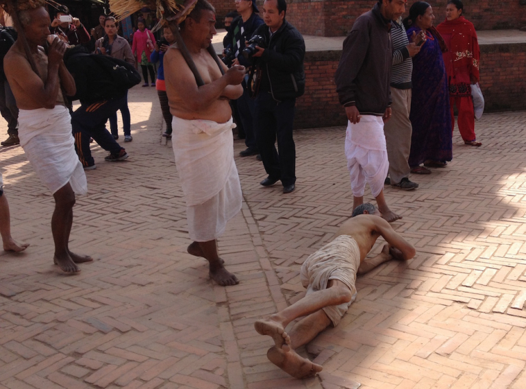 Man rolling on his side through the streets of Nepal