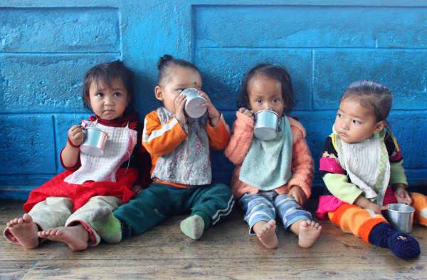 Four toddlers drink from metal cups