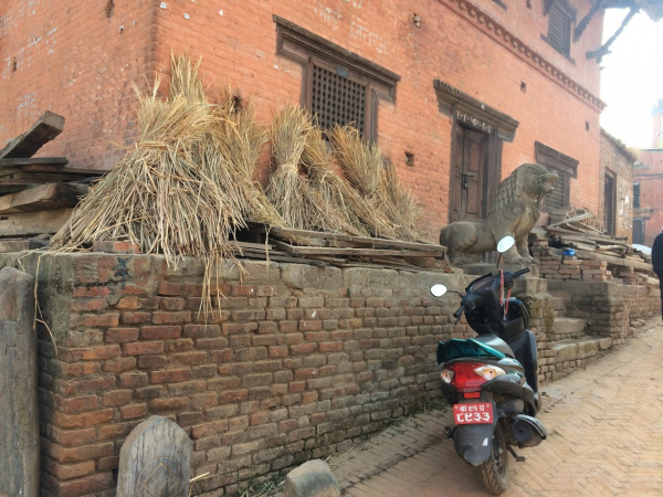 Moped leaning next to wall and local statues.