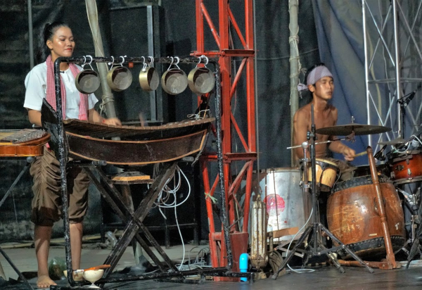 Woman plays a percussion instrument and man plays drums
