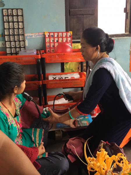 An Indian woman gets her blood pressure taken
