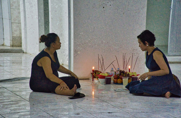 Two ladies talk while sitting around candles on tiled floor