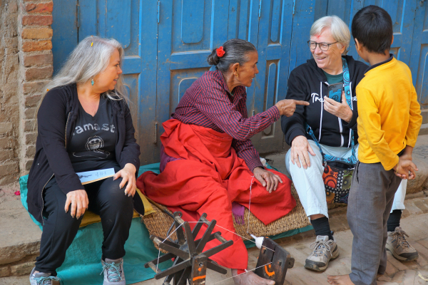 Trish and friends sitting talking with a wool spinner
