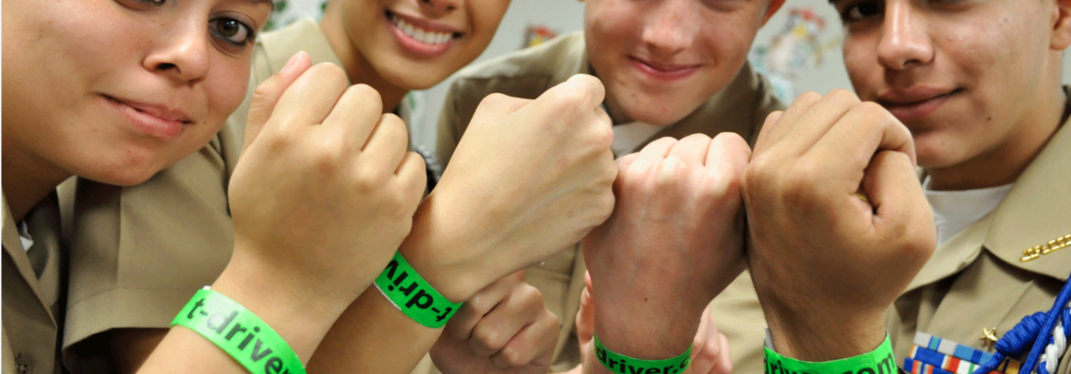 Four teens wearing a Safe Driving wrist band.