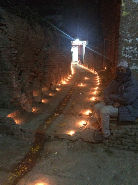 Person sits to side of Lights that line the streets of Nepal