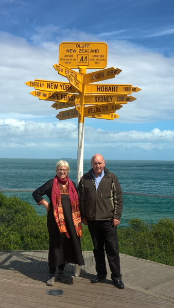 Trish standing with friend in front of a yellow, New Zealand Bluff sign pointing to locations around the world.