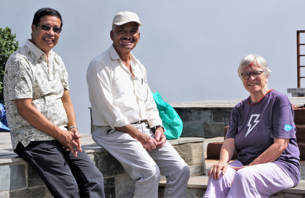 Trish sitting with two Nepalese men smiling for a photo