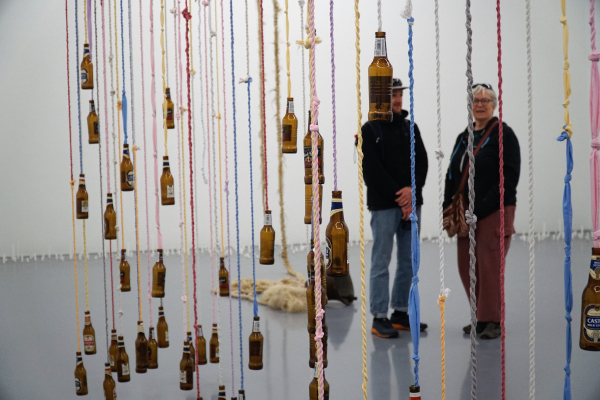 Trish and colleague looking at an Art exhibit of hanging bottles from colored rope