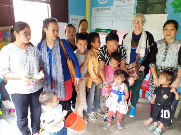 Trish smiling with Himalayan ladies and children
