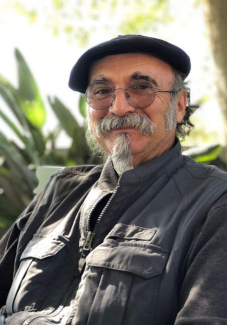 A sunny portrait of Jean-Francois Llorens in South Africa. Jean-Francois Llorens is wearing a beret hat and distinctive round glasses.
